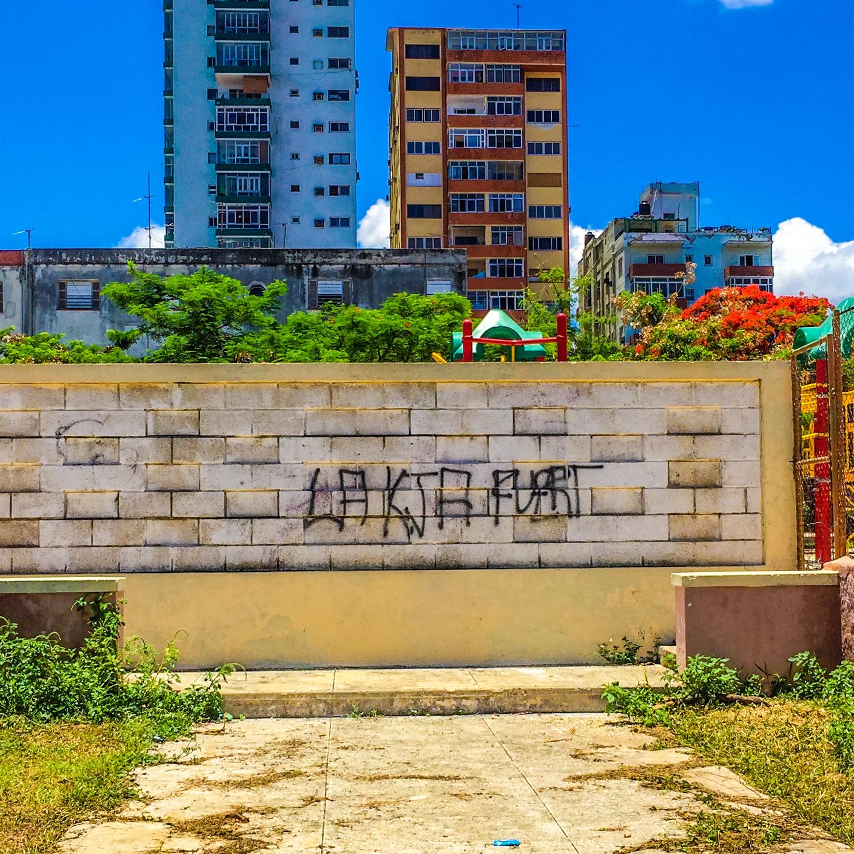 "A playground behind a wall with graffiti scrawled in skinny black aerosol saying ""La Kja Fuert"""